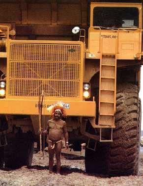 A Min warrior in full arms and bilas looks like a dwarf in front of a 190 t mining truck on a picture taken 1983